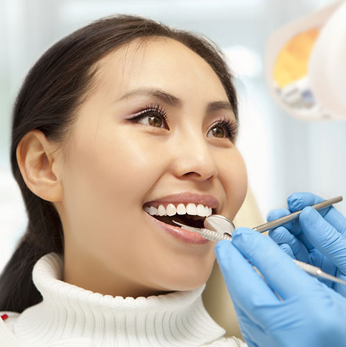 woman smiling at dentist teeth cleaning